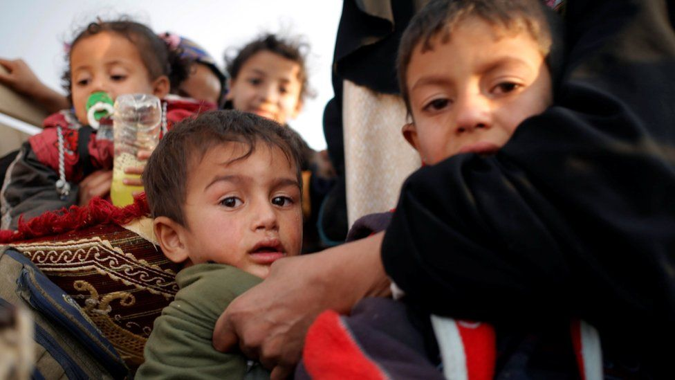 A newly displaced woman holds her sons in a truck at check point in Qayyara, east of Mosul on 26 October