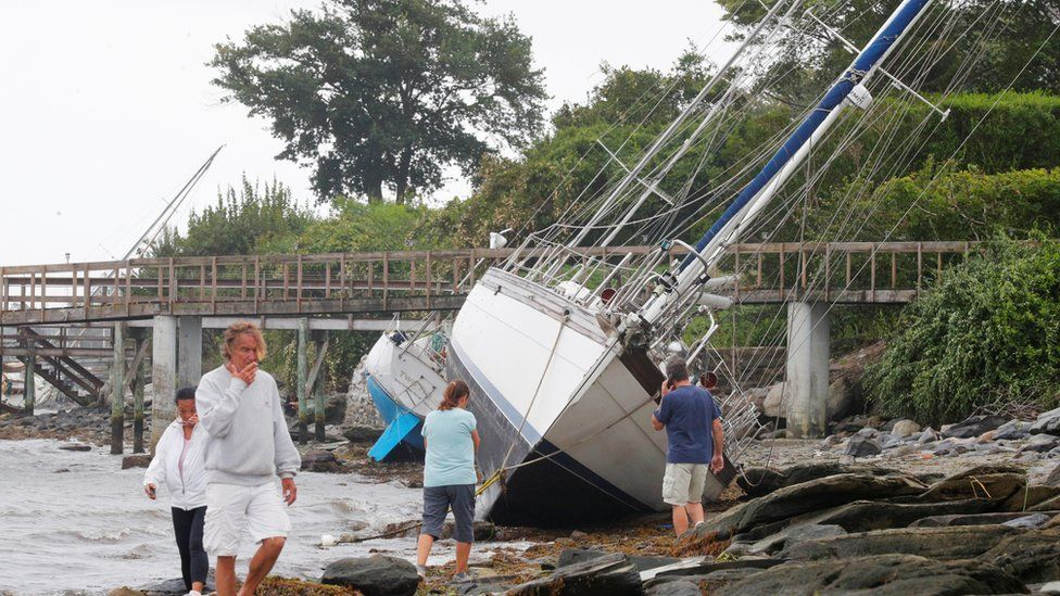 People walk past sailboats that came loose from their moorings and washed onshore during Tropical Storm Henri in Jamestown, Rhode Island, on 22 August, 2021.