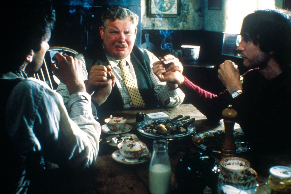 Uncle Monty (Richard Griffiths) sits at the cottage table with Withnail and Marwood