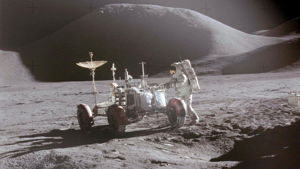 Astronaut David Scott approaches the Lunar Roving Vehicle (LRV) during the Apollo 15 mission, July 1971