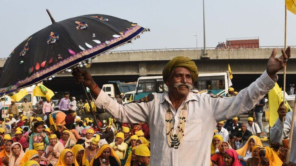 A farmer stands with an umbrella in Delhi during the protest