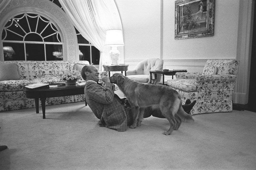 President Gerald R Ford plays with a dog in the family residence of the White House