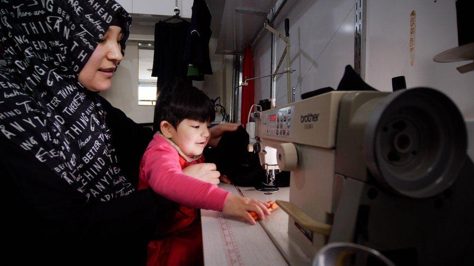 Kalbinur Tursan working in her tailor shop in 2019