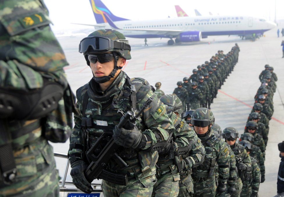 Paramilitary policemen board a plane as they head for an anti-terrorism oath-taking rally in Kashgar, from Urumqi, Xinjiang Uighur Autonomous Region, China, 27 February 2017.