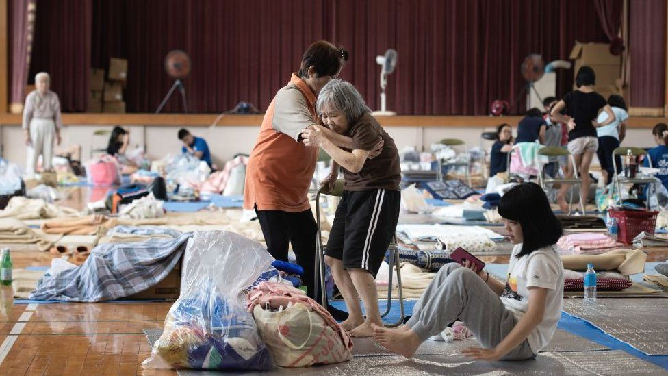 An elderly woman (C) is given assistance as people affected by the recent flooding rest at a makeshift shelter in Mabi, Okayama prefecture on July 11, 2018.