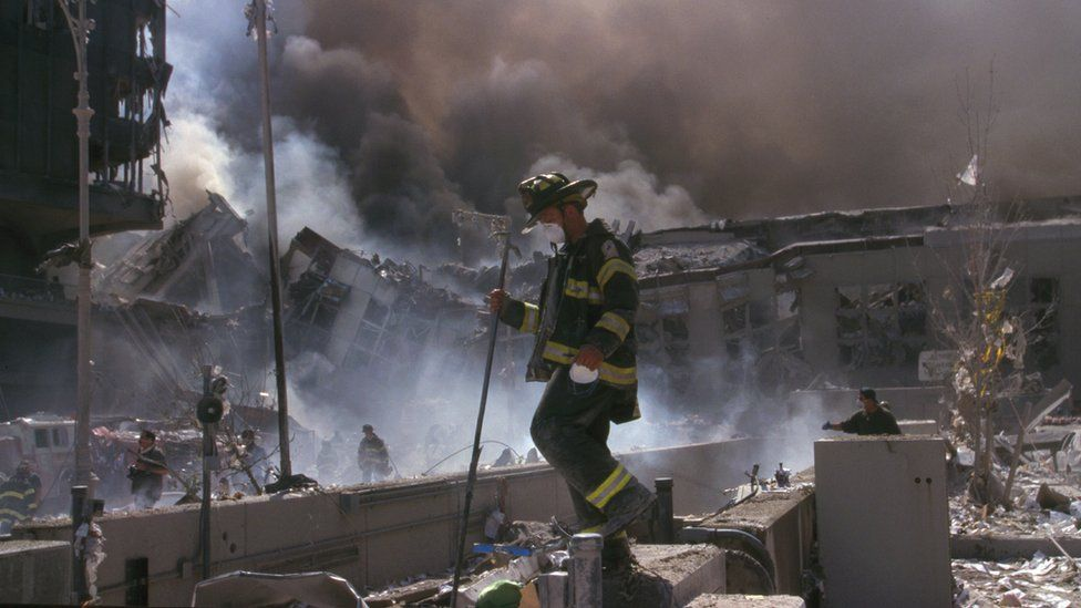 A firefighter walking through the rubble after 9/11