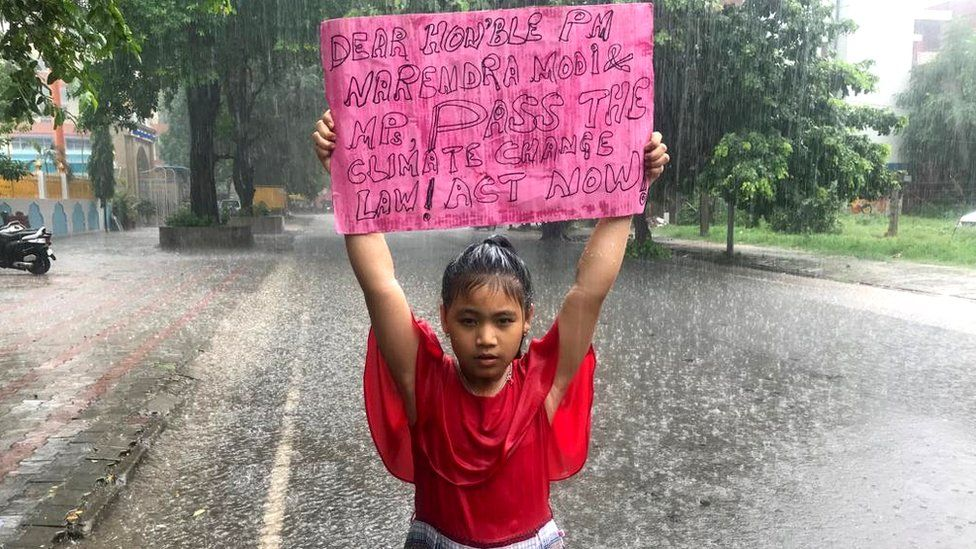 Licypriya Kangujam, eight, stands in the rain holding a sign urging the Indian government to pass a law on climate change, 2019