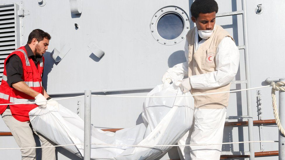 """Libyan Red Crescent workers carry a bag containing a body of a migrant who died when a boat sank off Libya""""s western coast on November 25, 2017"""