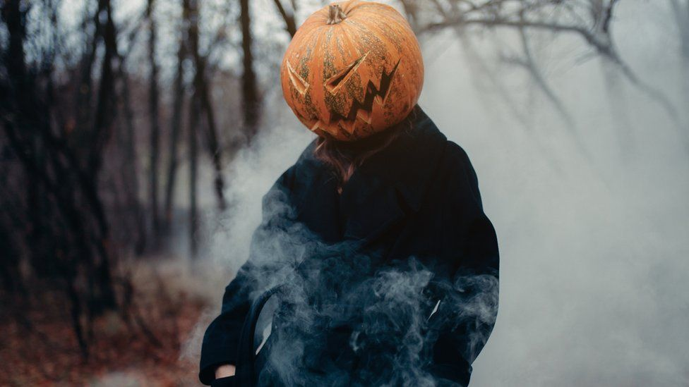 A man in a long black coat with a pumpkin instead of a head in a dark, damp and foggy forest.