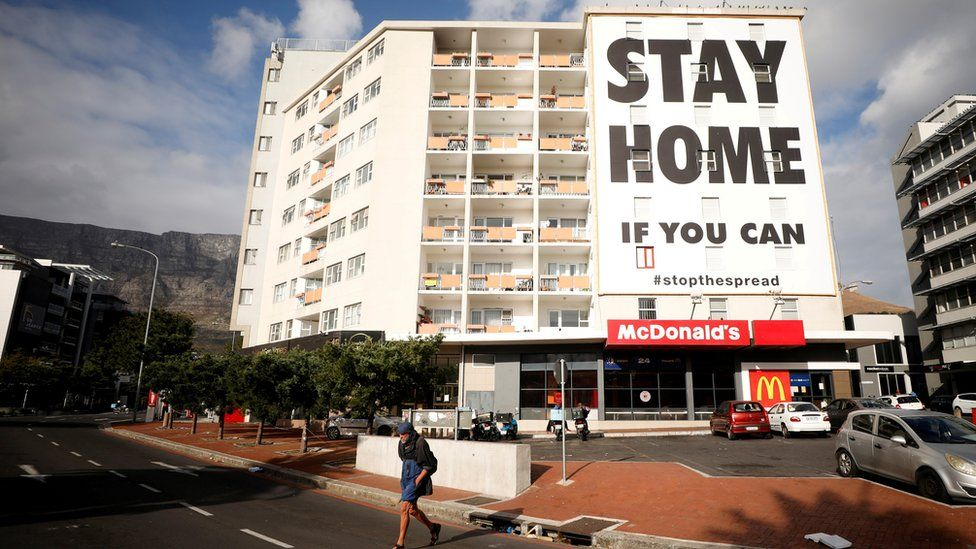 Man walks past a stay at home poster