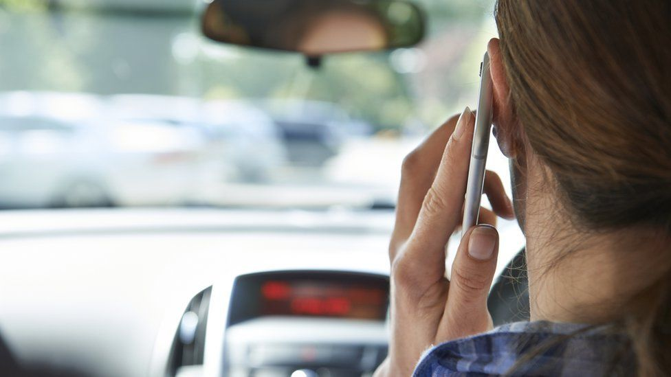 Woman on mobile phone in her car