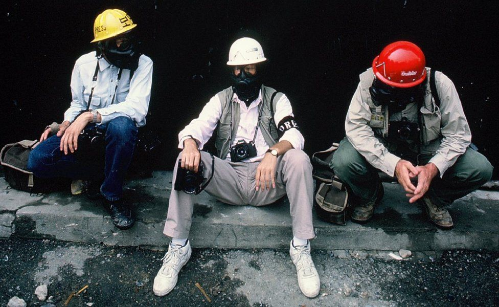 Charlie Cole sitting with two other men wearing gas masks and helmets