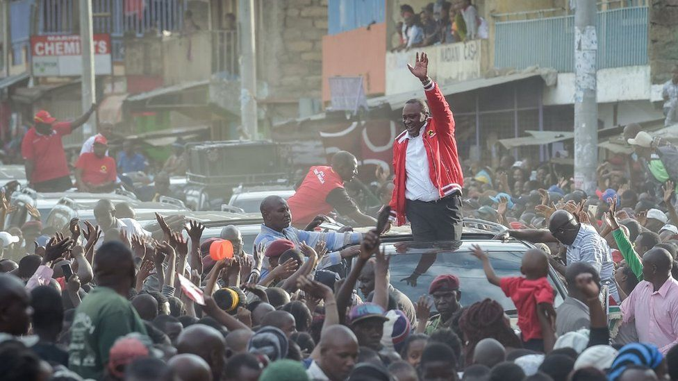 Kenya's President Uhuru Kenyatta gestures as he speaks from a car roof during a political rally in Nairobi, on October 23, 2017