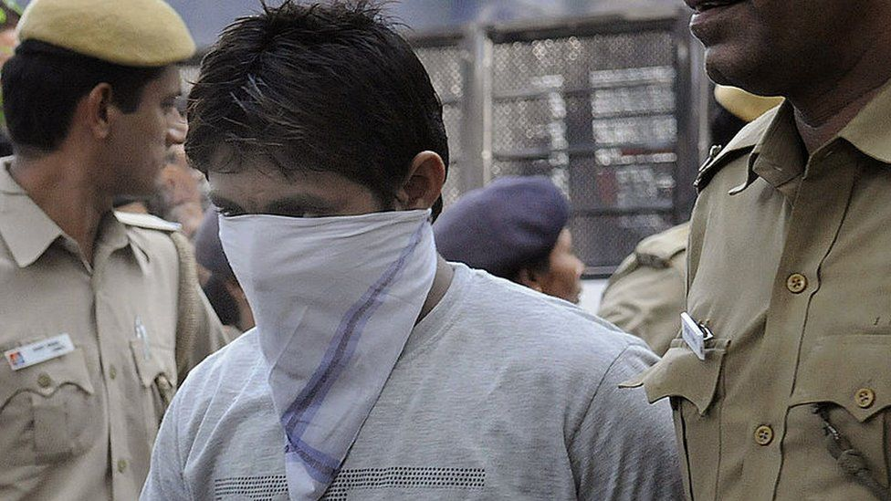 Indian police officials escort Pawan Gupta, one of those convicted in the Delhi gangrape case, to an appearance at the High Court in New Delhi on September 24, 2013