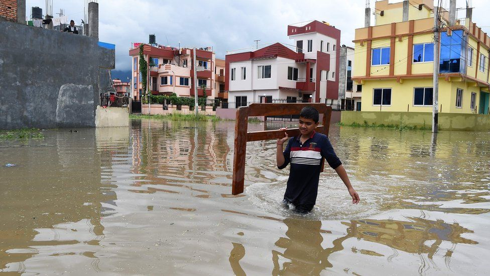 Nepali youth carries home goods along a water logged street in Patan, on the outskirts of Kathmandu