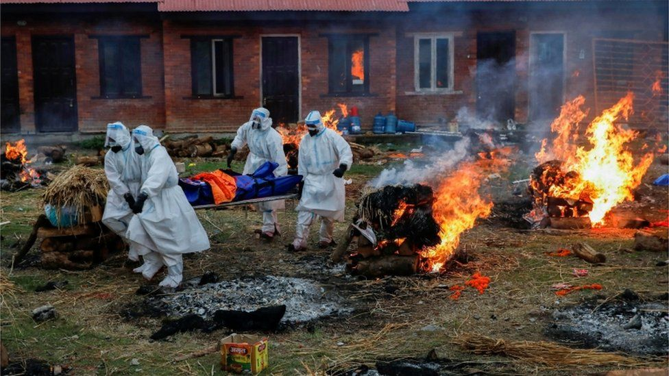 Nepalese soldiers in PPE carry a body away at a crematorium