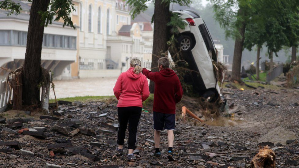 Two persons stand amid the debris near a damaged car and trees after flooding in Bad Neuenahr-Ahrweiler