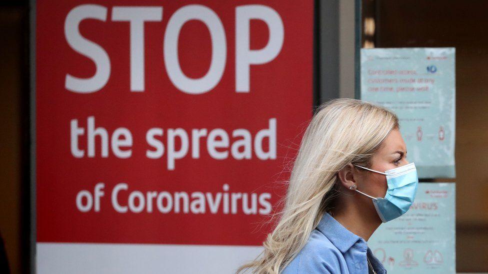 A woman walking past a coronavirus warning sign in Glasgow