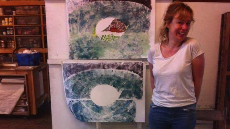 Jen Coles standing next to her own artwork