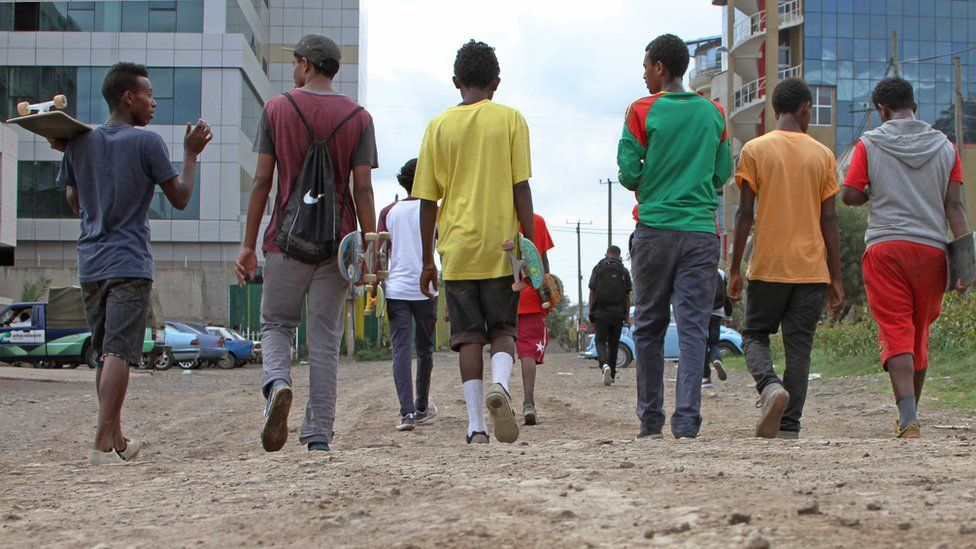 group shot of boys walking away holding skateboards