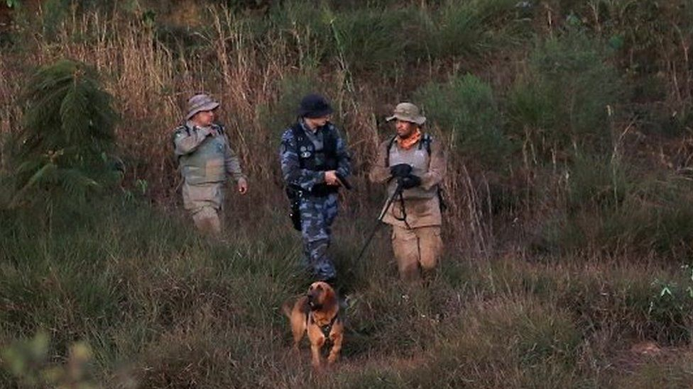 Police officers with a K-9 dog participate in a manhunt for suspected serial killer Lazaro Barbosa de Sousa in Cocalzinho de Goias, Goias state, Brazil June 22, 2021.