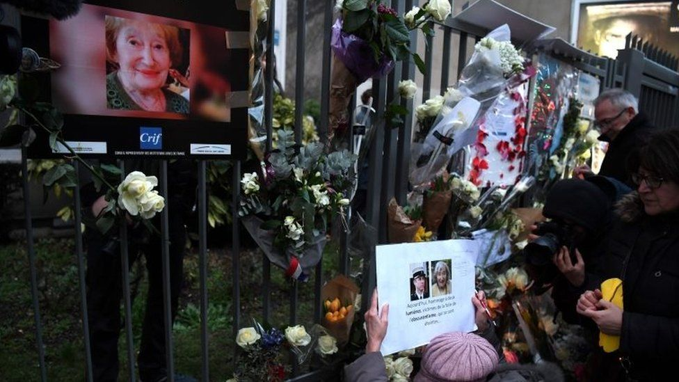 People lay flowers in front of the apartment in Paris where Mireille Knoll lived. Photo: 28 March 2018