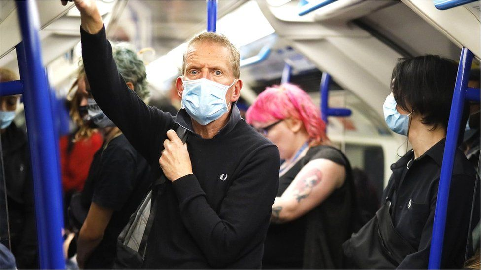 Man wearing a face mask on a London Underground train