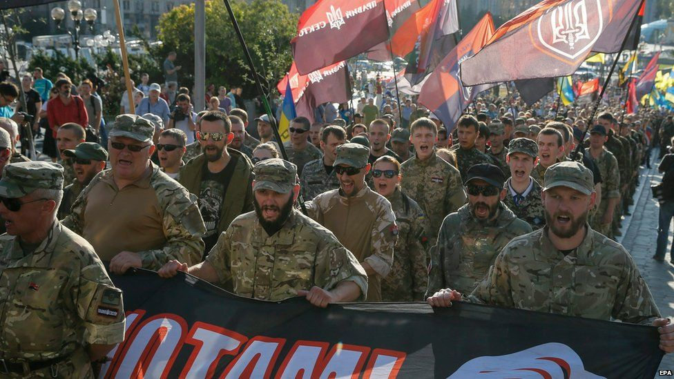 """Members and supporters of Right Sector and other ultra-right political parties hold poster with slogan""""Freedom to political prisoners"""" as they march during a protest in downtown Kiev, Ukraine, 3 July 2015."""