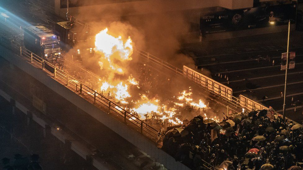 A police personnel vehicle is on fire as protesters and police clash on a bridge at The Hong Kong Poytechnic University on November 17, 2019 in Hong Kong, China.