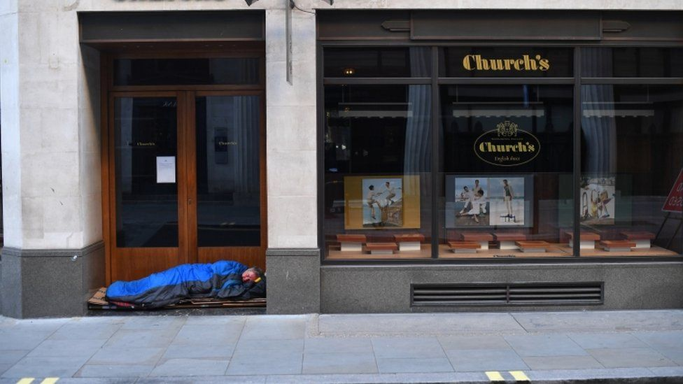 A man sleeps in the doorway of a shop in London