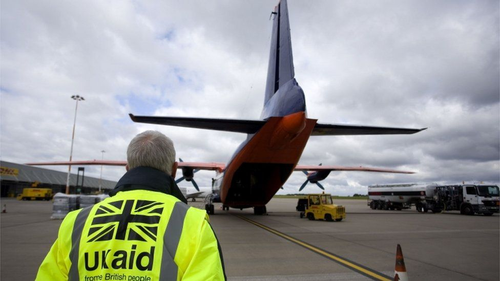 UK aid worker watches cargo being loaded on to a plane at East Midlands airport going to Iraq