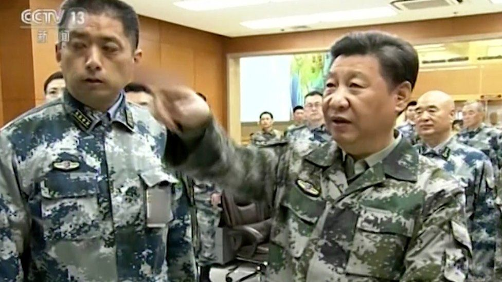 Xi Jinping, in military uniform, gestures during a tour of the military command centre in Beijing, 21 April 2016
