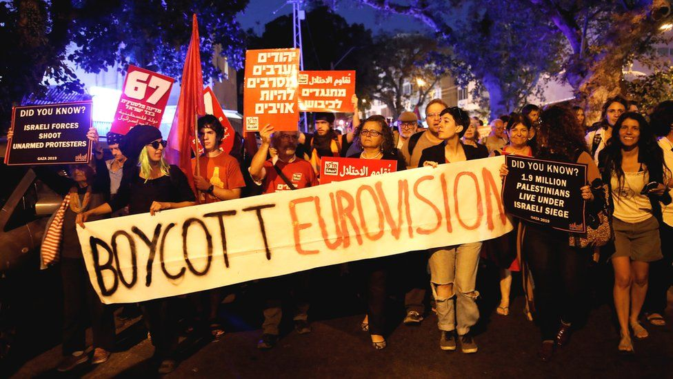 Protesters hold banners and placards as they take part in a demonstration calling for an end to Israel's policy towards Gaza and a boycott of the 2019 Eurovision Song Contest in Tel Aviv, Israel
