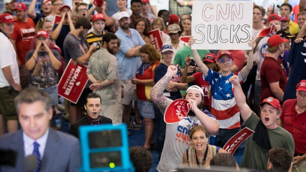 People shout behind CNN reporter Jim Acosta before a campaign rally for South Carolina Governor Henry McMaster featuring President Donald Trump at Airport High School June 25, 2018