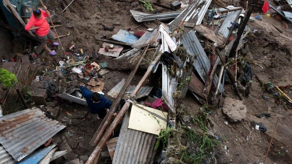A woman and her son look at the rubble after their house was devastated by the overflowing of a creek due to the torrential rains caused by the passage of tropical storm Amanda in San Salvador on May 31, 2020.
