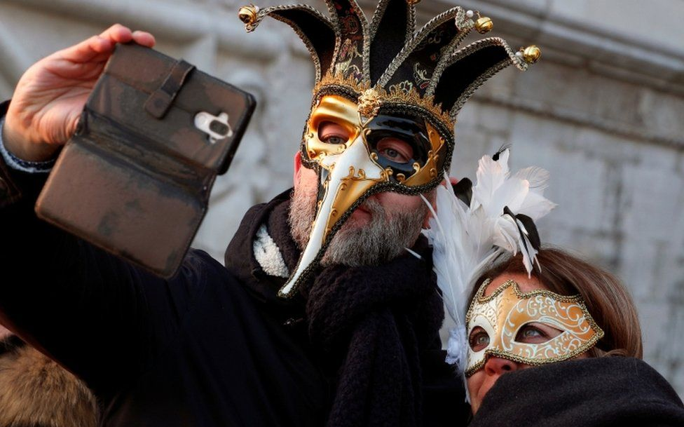 A masked couple takes a selfie during Carnival celebrations