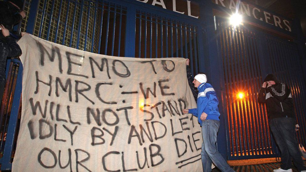 Fans raise a banner on the gates of Ibrox Stadium on February 14, 2012 in Glasgow, Scotland