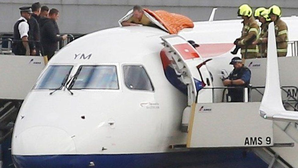 James Brown lying on plane as police and fire-fighters watch on