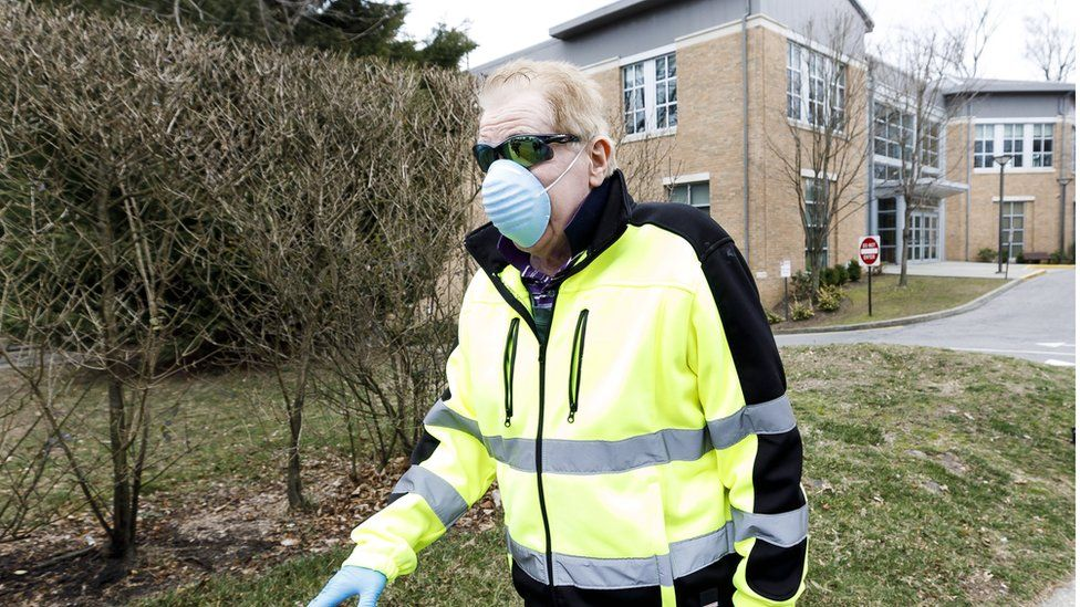 Nicholas Walsh, of New Rochelle, wears a protective mask as he walks past the Young Israel of New Rochelle synagogue (R) in New Rochelle, New York, USA, 10 March 2020.