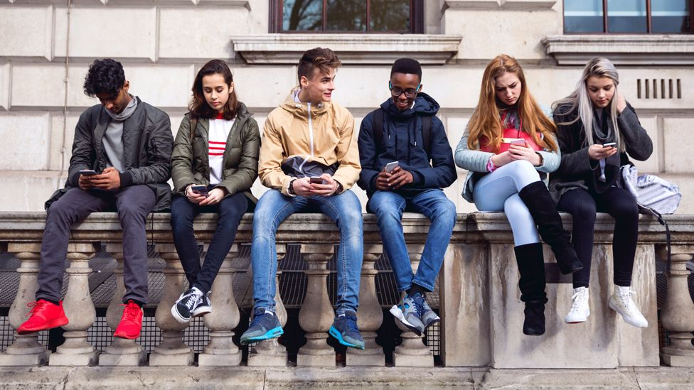 Teenagers sitting on a wall