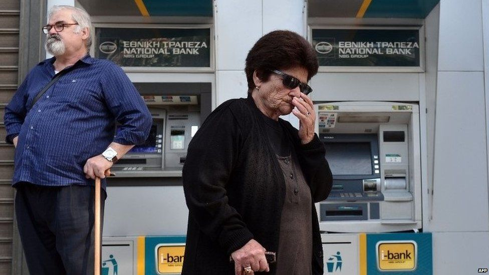 People wait by cash machines in Greece, 29 June 2015