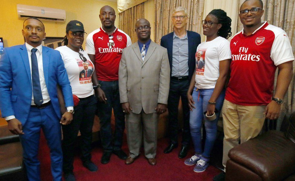 Former soccer coach Arsene Wenger (3-R) pose for a photo with local Arsenal fans upon arrival at the Roberts International Airport in Harbel, Liberia, 22 August 2018.