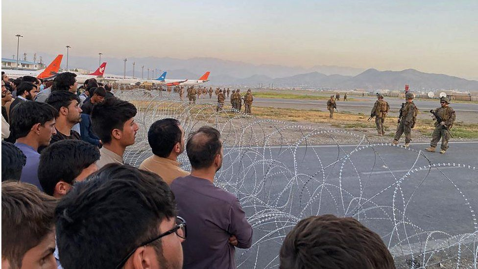 Afghans crowd at the airport as US soldiers stand guard in Kabul on 16 August 2021.