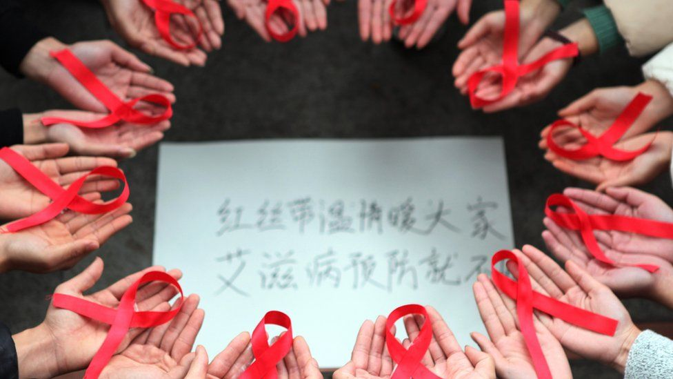 This picture taken on November 30, 2015 shows volunteers holding red ribbons above a piece of paper written in Chinese that reads ''Red ribbons bring warmth to everyone to prevent AIDS'