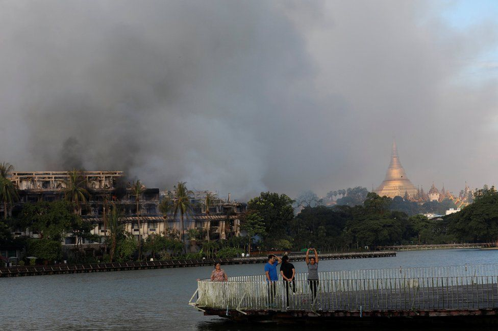 People do exercises near a fire at Kandawgyi Palace hotel in Yangon, Myanmar October 19, 2017 .