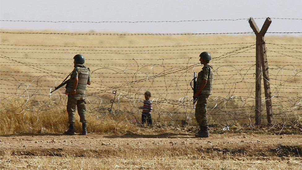 Turkish soldiers stand guard as a Syrian refugee boy waits behind the border fences to cross into Turkey on the Turkish-Syrian border on 5 June