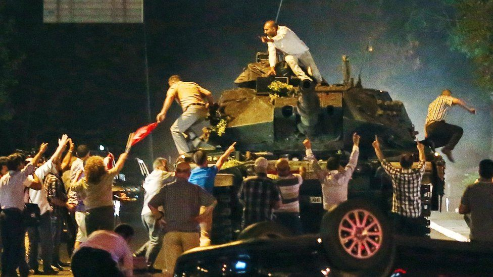 Turkish people climb on a tank attempting to stop the coup attempt in the early morning of July 16th in Ankara