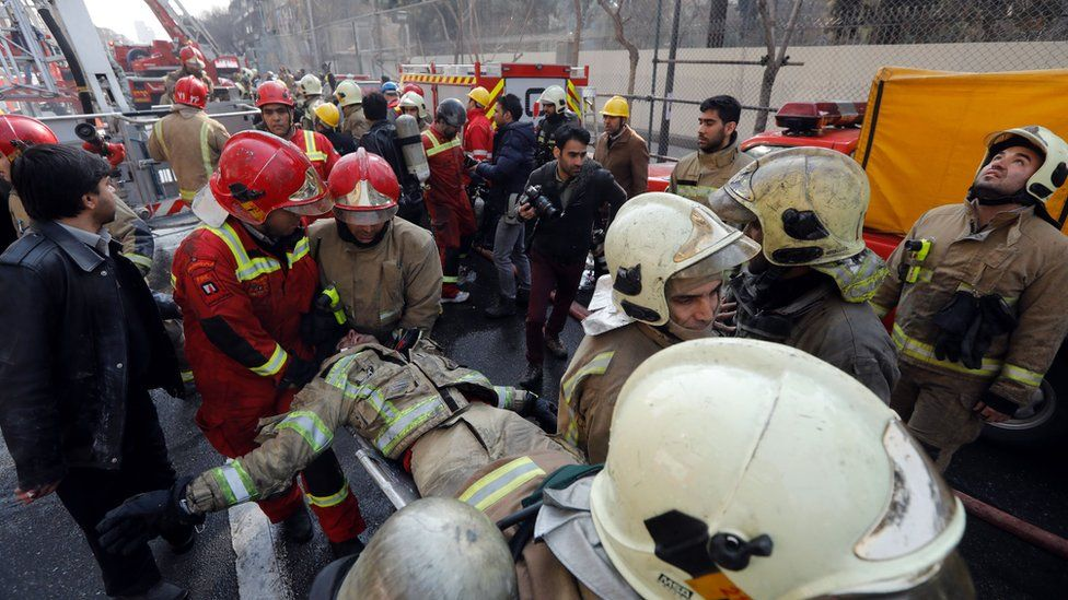A wounded fireman is carried from the collapsed Plasco building in Tehran, Iran (19 January 2017)
