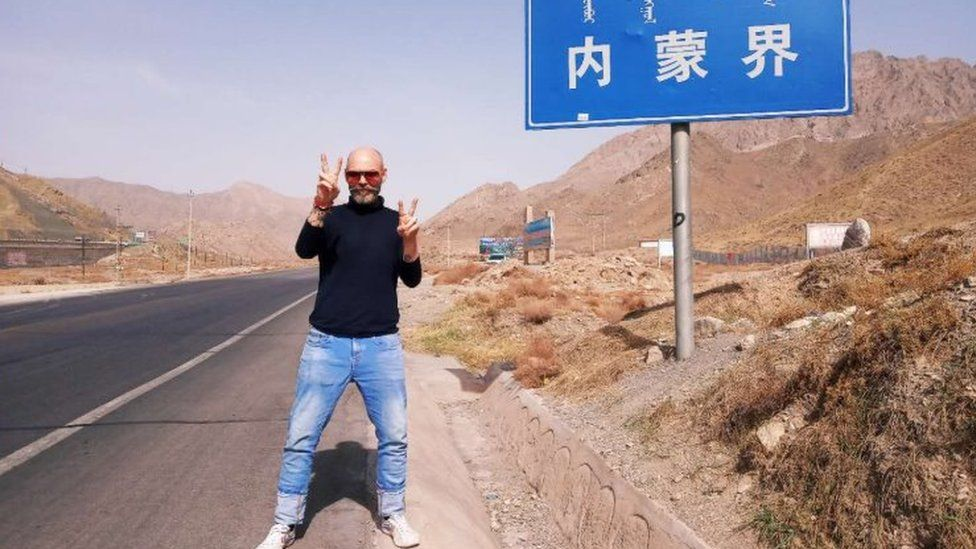 Michael Hope stands beside a Chinese road sign