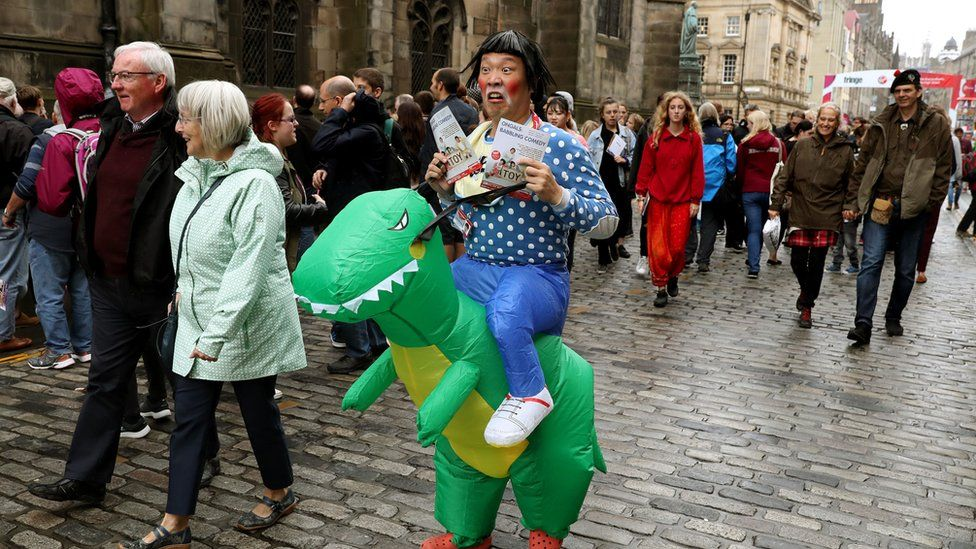 Performer advertises his show on the Royal Mile